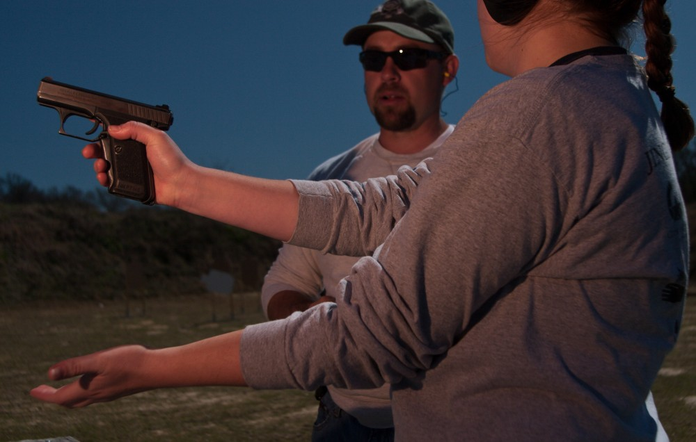 A student gets a lesson in handgun safety from her instructor prior to shooting at a firing range near Hearne, TX.