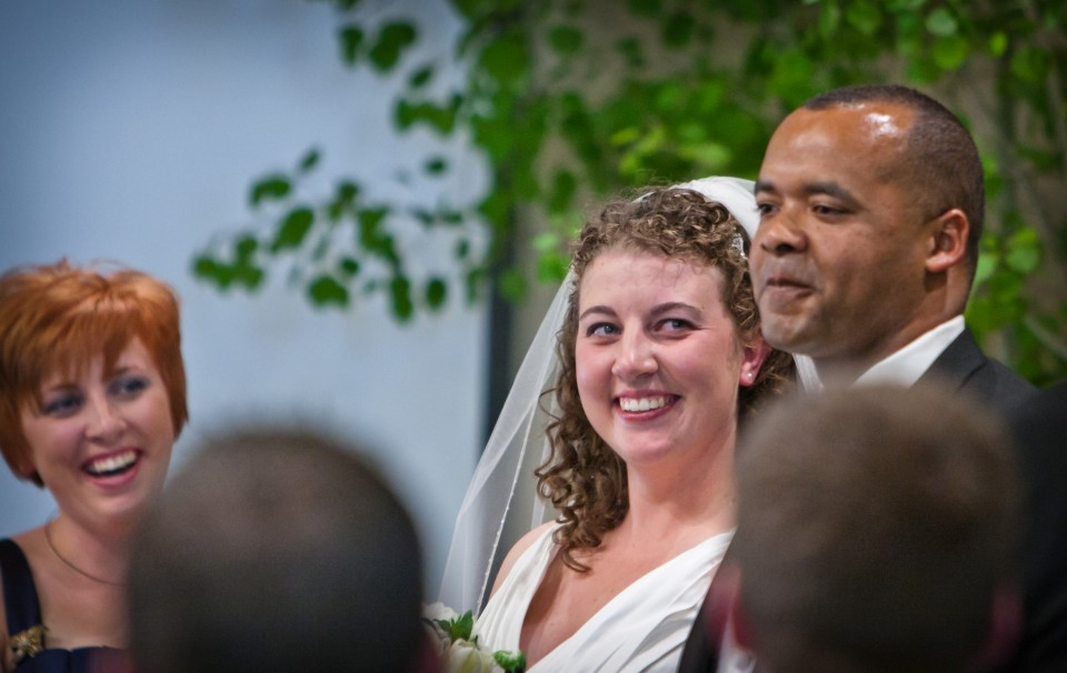 A bride sneaks a glance at her new husband as they are introduced as man and wife to friends and family.