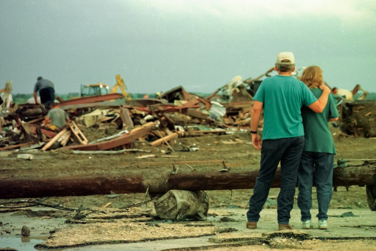 An unidentified couple watches as volunteers and rescue workers dig through the debris of a recycling facility in Jarrell, Texas. The plant was destroyed by a tornado on May 27, 1997. © Temple Daily Telegram/Matthew Crawley