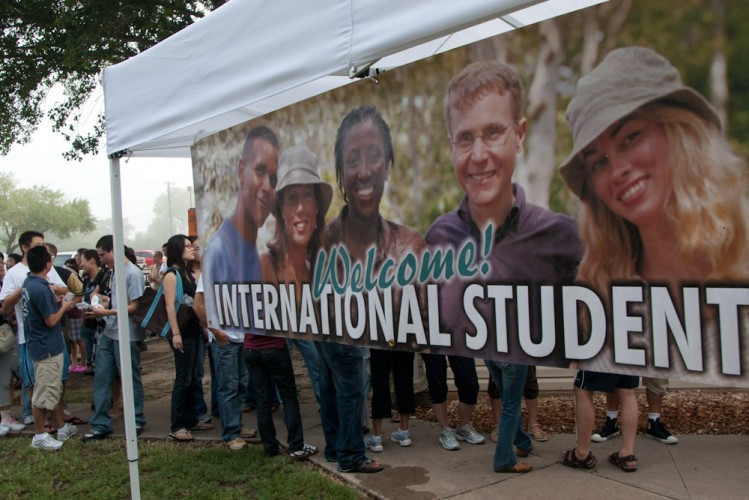 A sign welcomes international students as they stand in line for a household goods giveaway
