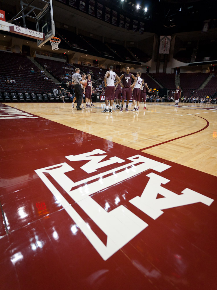 The Texas A&M logo on the edge of the court at Reed Arena with players in background