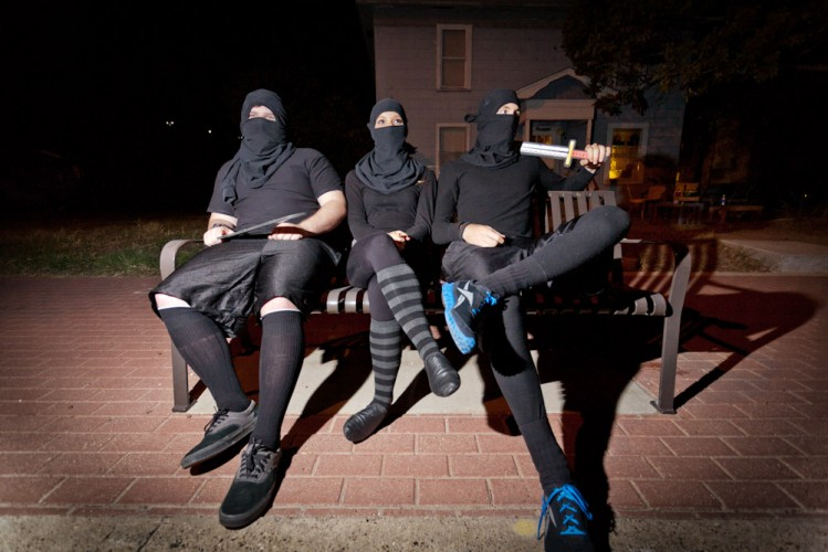 Three college students dressed as ninjas sit on the bench waiting for a bus