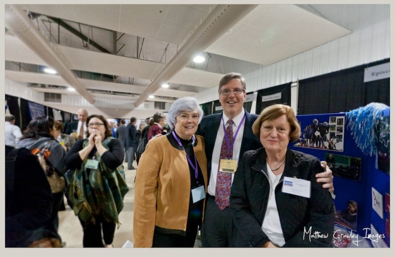A man and two women pose in an exhibit hall