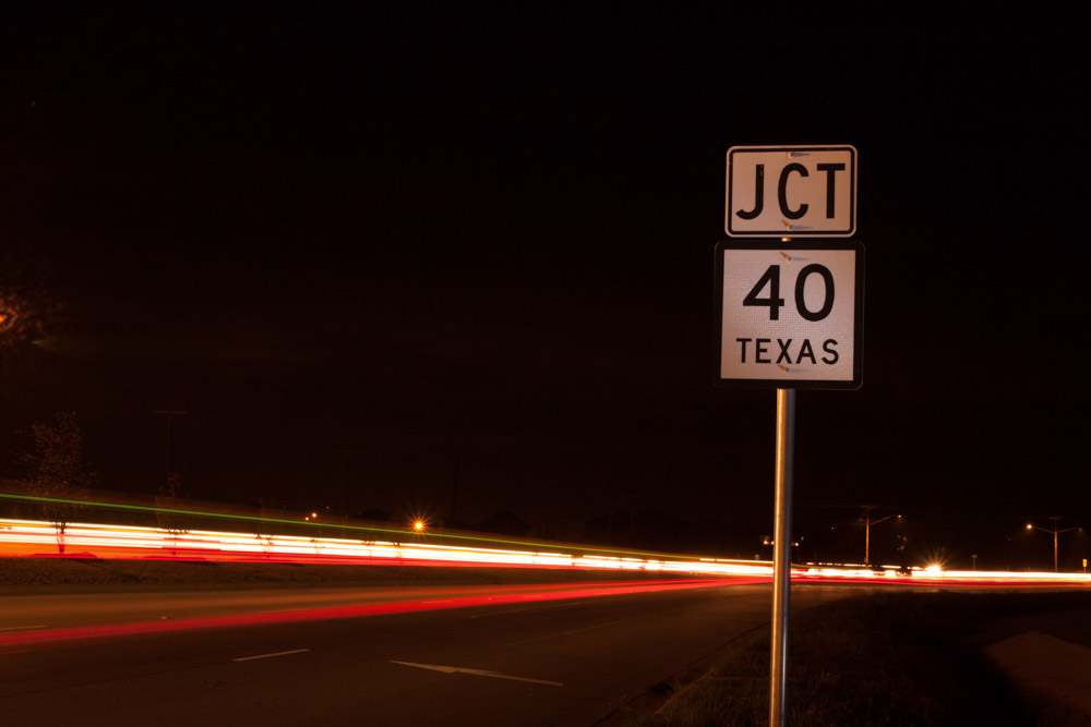 Tailights form streaks on road next to Texas 40 Highway Sign